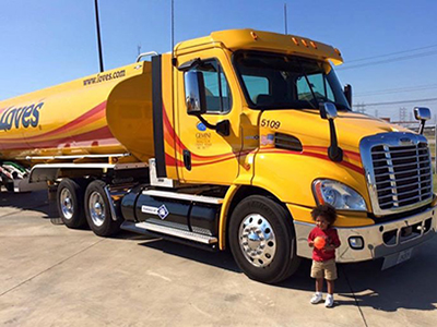 boy smiles next to Love's truck