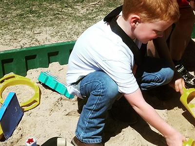 child building in sandbox