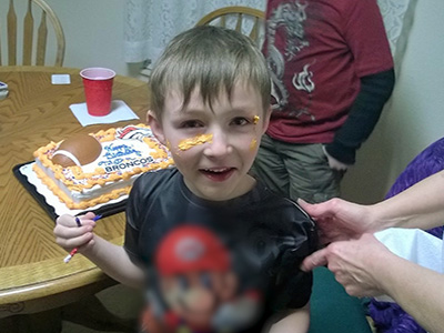 young boy smiles with birthday cake